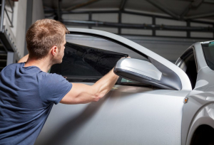 A man putting window tinting film on a car
