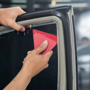 Skilled worker applying window tints on car door.